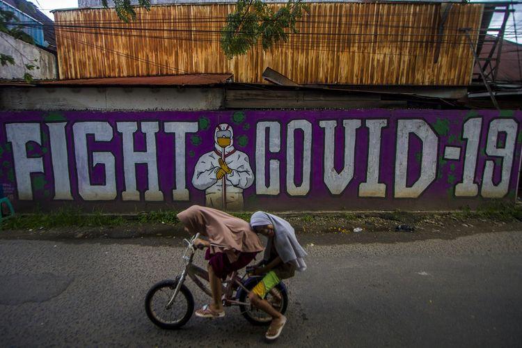 Dua orang bocah mengayuh sepedanya di dekat mural bertema COVID-19 di Banjarmasin, Kalimantan Selatan, Senin (17/5/2021). Berdasarkan data Dinas Kesehatan Kota Banjarmasin, selama bulan Ramadhan lalu jumlah kasus aktif COVID-19 mengalami penurunan dari 253 kasus pada tanggal 13 April 2021 menjadi 166 kasus pada tanggal 15 Mei 2021 karena adanya pemberlakuan larangan mudik dan penutupan lokasi wisata selama libur lebaran. ANTARA FOTO/Bayu Pratama S/wsj.