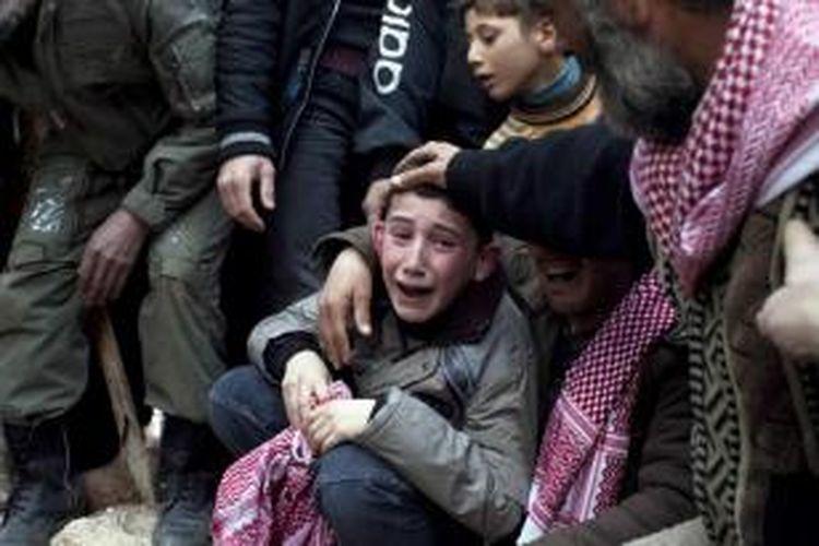 Ahmed (tengah) menangisi ayahnya Abdulaziz Abu Ahmed Khrer, yang tewas terbunuh oleh sniper anggota pasukan pemerintah, saat pemakaman ayahnya di Idlib, utara Suriah, 8 Maret 2012.