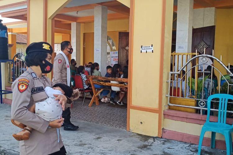 PHOTO:Brigpol Caesilia Ina Korebima, anggota Polres Ngada, Nusa Tenggara Timur (NTT), menggendong bayinya saat bertugas melakukan pengamanan perayaan Natal
