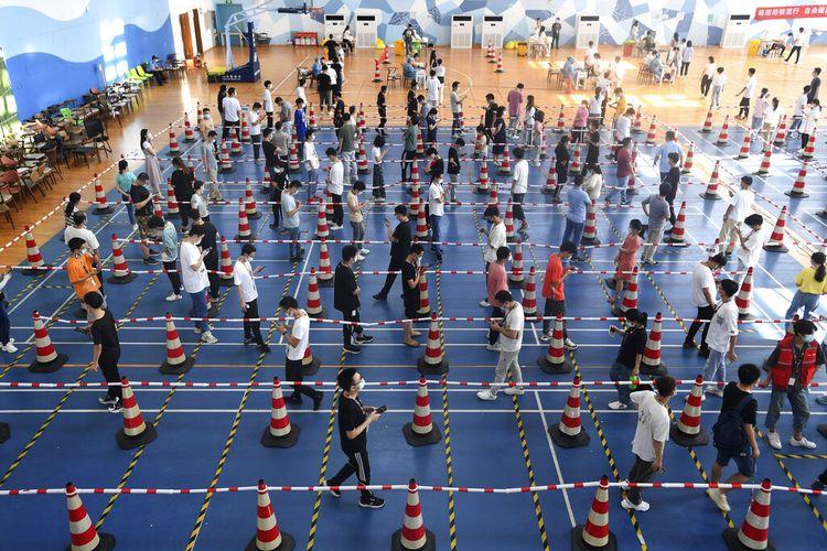 Pekerja dari perusahaan <a href='https://manado.tribunnews.com/tag/china' title='China'>China</a> Star Optoelectronics Technology (CSOT) berbaris untuk tes virus corona massal di gym selama putaran tes Covid-19 di Wuhan di provinsi Hubei, <a href='https://manado.tribunnews.com/tag/china' title='China'>China</a> tengah pada 5 Agustus 2021.