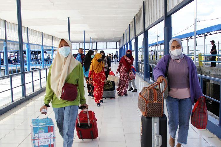 Sejumlah pemudik dari Kepulauan Riau berjalan menuju terminal ketibaan di Pelabuhan Bandar Sri Junjungan Dumai, Riau, Minggu (25/4/2021). Dua pelabuhan di Dumai, Pelabuhan Roro Purnama dan Bandar Sri Junjungan mulai ramai disinggahi pemudik Hari Raya Idul Fitri 2021 dan kedua pelabuhan tersebut digunakan sebagai tempat transit pemudik menuju kampung halamannya seperti ke Pulau Rupat, Sumbar, Jambi dan Sumut. ANTARA FOTO/Aswaddy Hamid/aww.