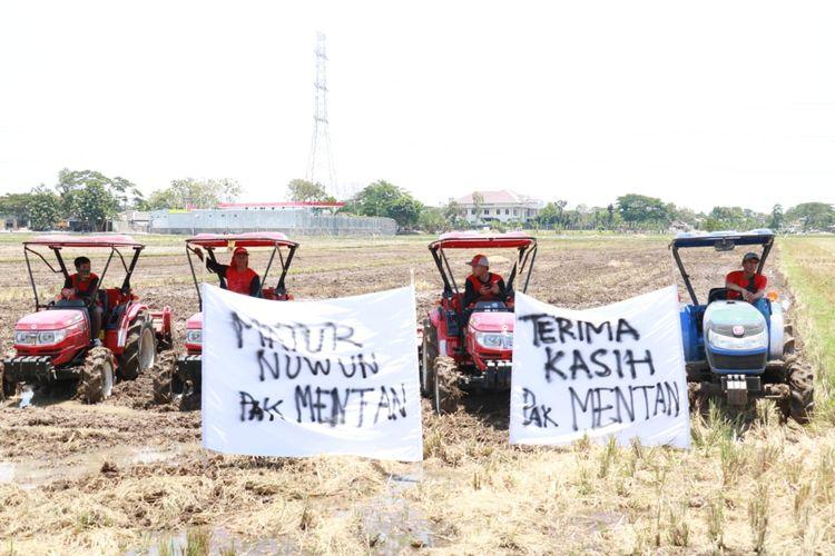 Beberapa petani sedang mengibarkan spanduk bertuliskan tanda terima kasih kepada Menteri Pertanian.