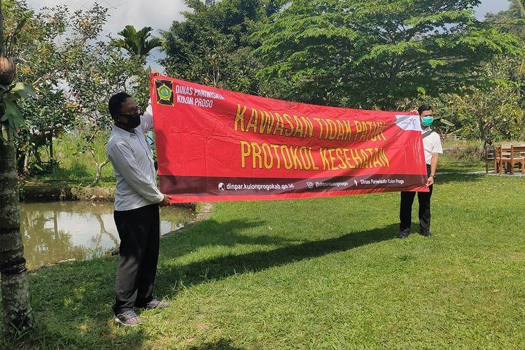 Spanduk merah yang disiapkan untuk menutup obyek wisata bandel tidak patuh protokol kesehatan si Kulon Progo, Daerah Istimewa Yogyakarta.