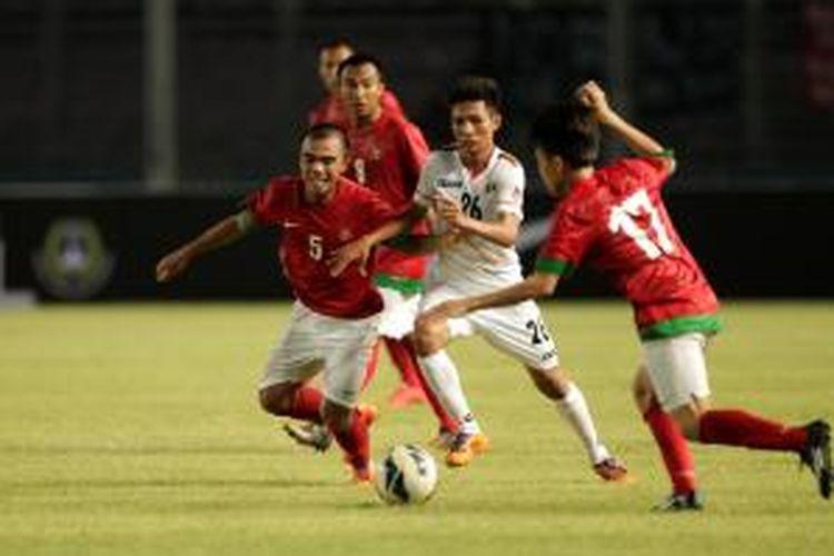 Pemain Indonesia U-19 M Fatchu Rohman (kiri) beradu dengan pemain Myanmar U-19 dalam pertandingan persahabatan di Stadion Utama Gelora Bung Karno, Senayan, Jakarta, Senin (5/5/2014). Pertandingan berakhir imbang 1-1.