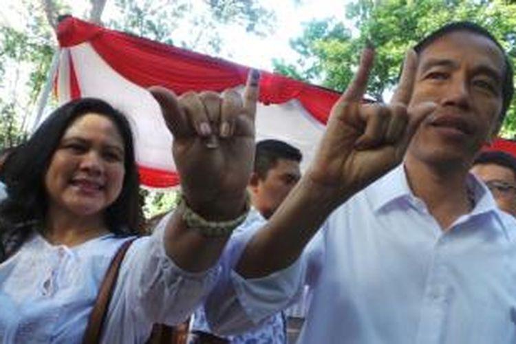 Gubernur Jakarta Joko Widodo dan sang istri Iriana memamerkan jari kelingkingnya usai menggunakan hak suara di TPS 27, Menteng, Jakarta Pusat, Rabu (9/4/2014).