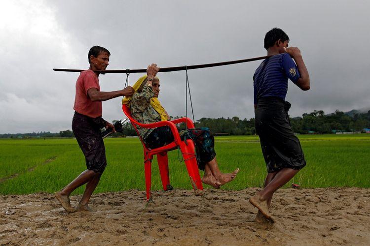 Dua lelaki Rohingya membawa seorang wanita tua karena tidak bisa berjalan setelah menyeberangi perbatasan, di Teknaf, Bangladesh, Jumat (1/9).