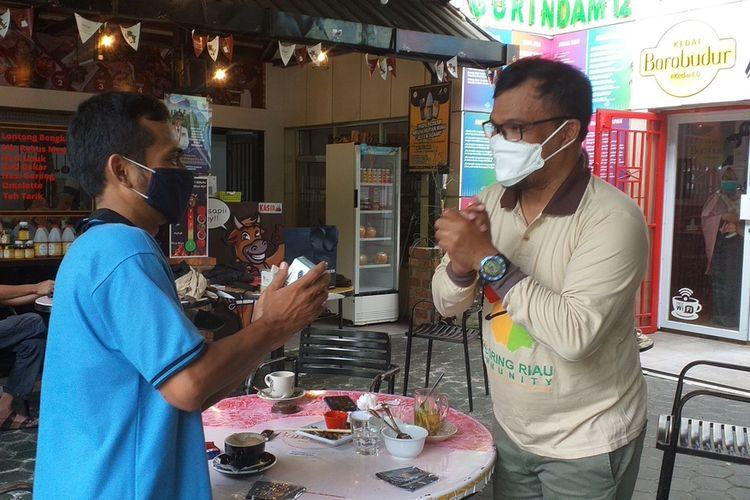 Rudi Fajar (kanan) meminjamkan Oximeter kepada salah satu warga yang membutuhkan, karena ada saudaranya positif Covid-19 yang isolasi mandiri, di Kota Pekanbaru, Riau, Sabtu (31/7/2021) siang.