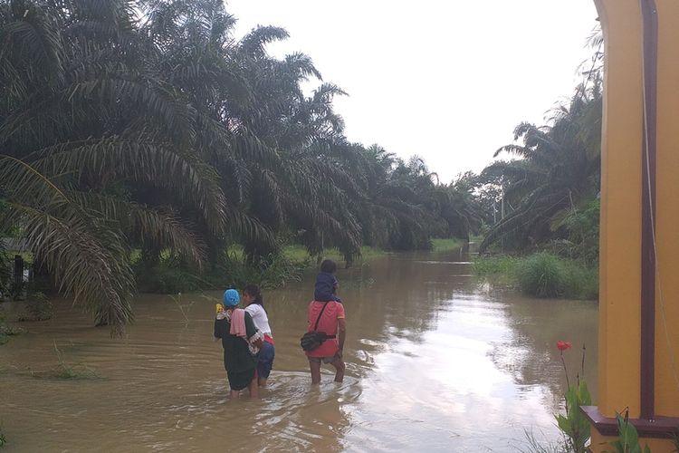 Warga mengarungi banjir untuk menuju rumahnya di Desa Sontang, Kecamatan Bonai Darussalam, Kabupaten Rohul, Riau, Jumat (29/11/2019).