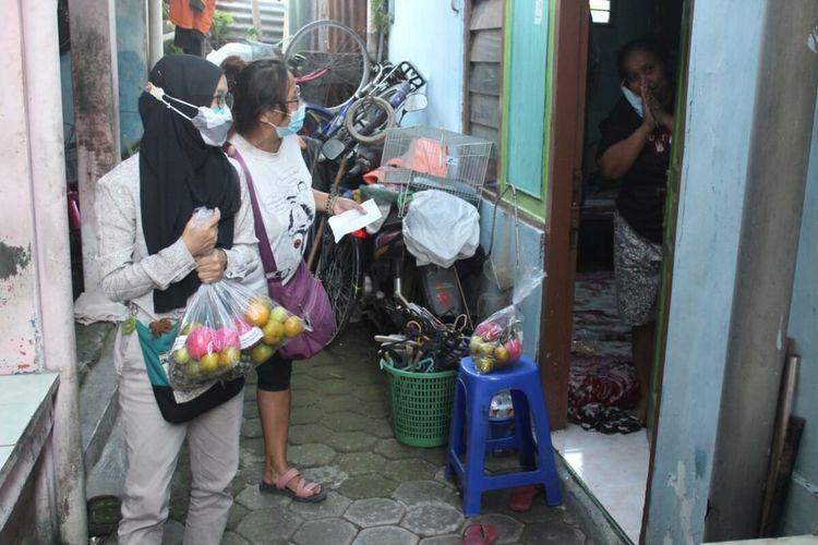 Mahasiswa ISI Solo memberikan paket buah-buahan kepada warga yang sedang menjalani isolasi mandiri di Pucangsawit, Jebres, Solo, Jawa Tengah, Sabtu (24/7/2021).