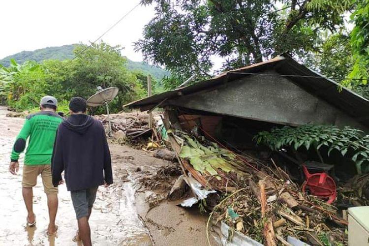 Warga melintas di dekat rumah yang rusak akibat banjir bandang di Adonara Timur, Flores Timur, NTT, Senin (5/4/2021). Berdasarkan data BNPB hingga senin siang, korban meninggal dunia akibat banjir bandang di Flores Timur mencapai  68 jiwa. ANTARA FOTO/Pion Ratuloli/wpa/wsj.