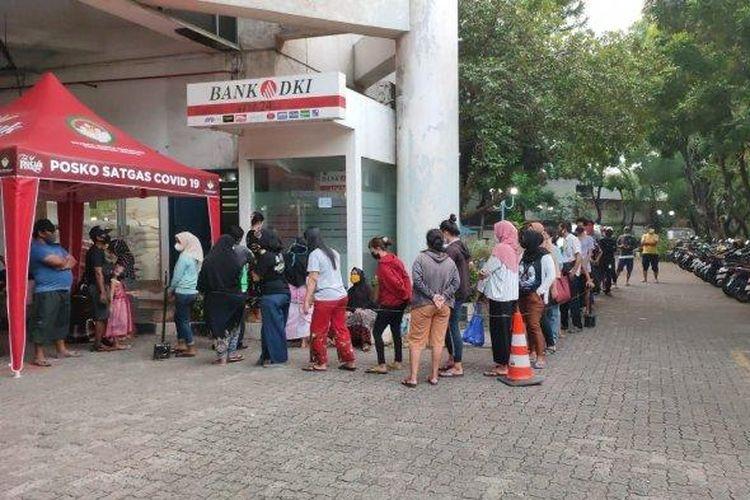 Antrean warga yang ingin mencairkan BST di ATM Bank DKI mengular di Gedung Mitra Praja, Tanjung Priok, Jakarta Utara, Senin (19/7/2021) sore.