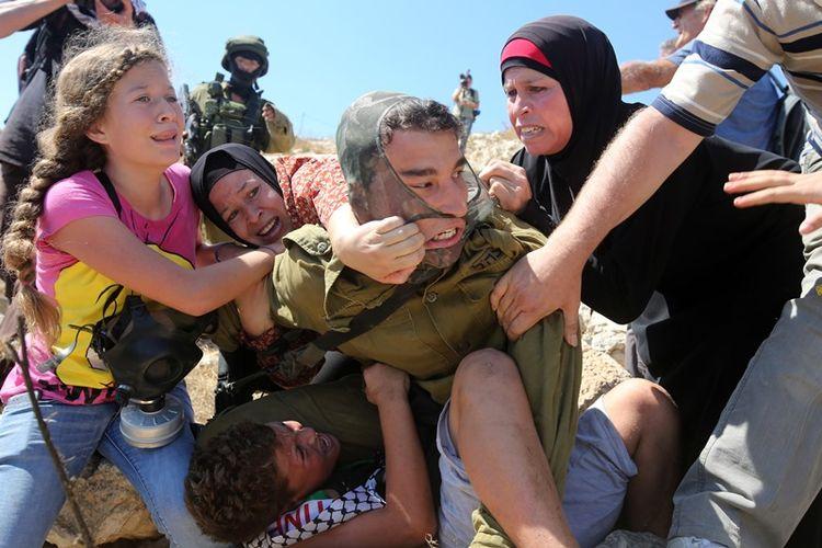 Ahed Tamimi (kiri) ketika bersitegang dengan seorang pasukan Israel. Tamimi dan keluarganya ditangkap militer setelah beredar video dirinya menampar serdadu Israel yang berjaga di Tepi Barat.