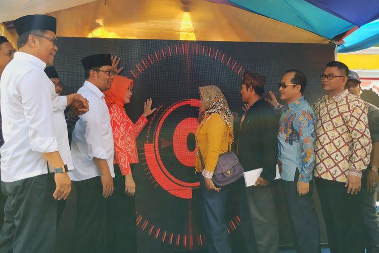 Menteri Kominfo Rudiantara (kiri) dan Gubernur Jabar Ridwan Kamil (kiri dua) bersama pejabat lain serta masyarakat saat peluncuran Desa Digital di Desa Sirnarasa, Cikakak, Sukabuni, Jawa Barat, Minggu (14/4/2019).