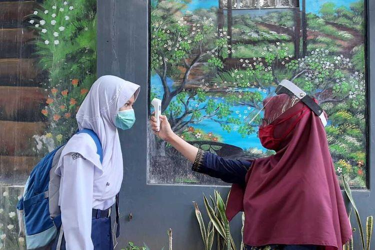 Guru mengecek suhu tubuh siswa SMP Negeri 6 Purwokerto, Kabupaten Banyumas,  Jawa Tengah, Selasa (20/10/2020).