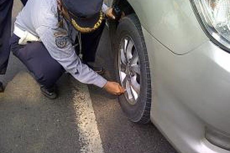 Seorang petugas sedang mencabut pentil ban dan mengempiskannya di Jalan Pemuda, Jumat (27/9/2013). Kendaraan tersebut menyalahi aturan dengan memarkirkan kendaraannya sembarangan.