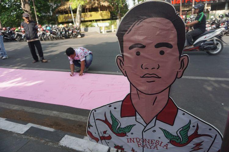 Warga membubuhkan tanda tangan dukungan terhadap putra sulung Presiden Jokowi, Gibran Rakabuming Raka maju Pilkada Solo 2020 di Jalan Bhayangkara Solo, Jawa Tengah, Minggu (3/11/2019).