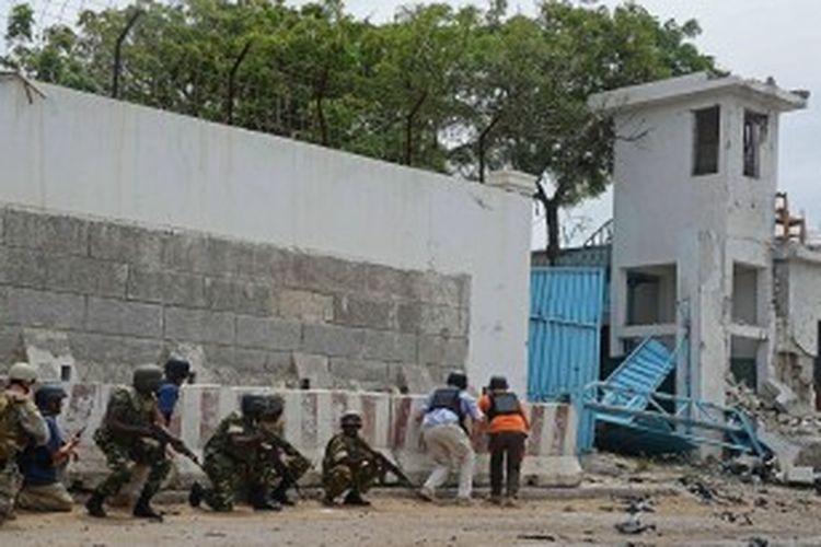 Para tentara AMISOM berlindung setelah gerilyawan Shebab yang punya kaitan dengan Al-Qaeda menembak mereka saat menuju ke kompleks Perserikatan Bangsa-Bangsa (PBB) di Mogadishu pada tanggal 19 Juni 2013.