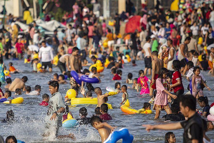 Pengunjung bermain air di Pantai Karnaval Ancol, Jakarta, Kamis (6/6/2019). Hingga sore ini tercatat sekitar 100 ribu pengunjung memanfaatkan waktu libur Lebaran 2019 bersama keluarga di Taman Impian Jaya Ancol.