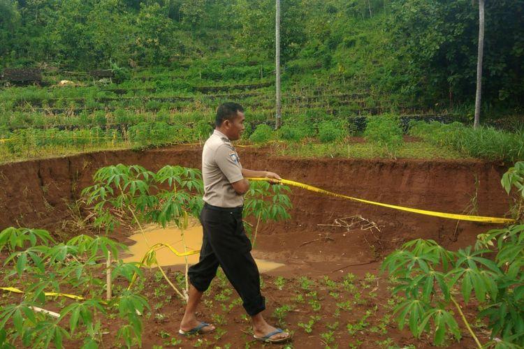 Polisi memasang garis polisi untuk mengantisipasi warga mendekati tanah ambles di Ngondel Kulon, Desa Krambilsawit, Gunungkidul.