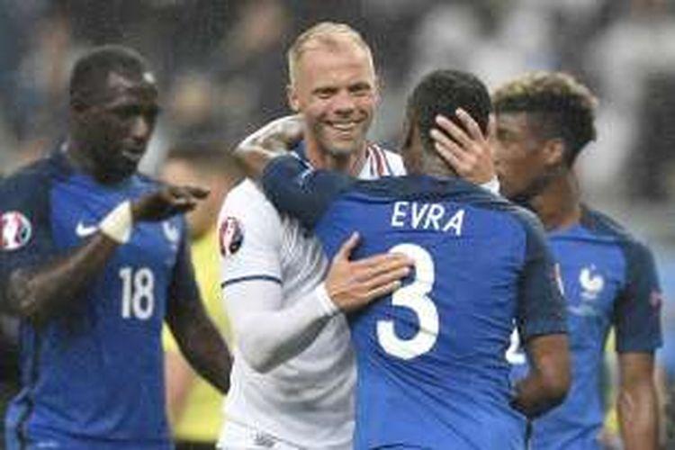 Pemain tim nasional Eslandia, Eidur Gudjohnsen, memeluk pemain Prancis, Patrice Evra, seusai laga perempat final Piala Eropa 2016 di Stade de France, 3 Juli 2016.