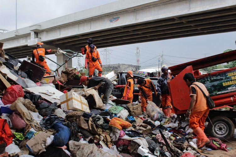 Para petugas Penanganan Prasarana dan Sarana Umum (PPSU) DKI Jakarta mengangkut sampah yang menggunung di bawah Tol Becakayu, Cipinang Melayu, Jakarta Timur, Rabu (8/1/2020). Tumpukan sampah ini berasal dari perumahan warga RW 03, 04, 10, 11, dan 12 Cipinang Melayu, Jakarta Timur.