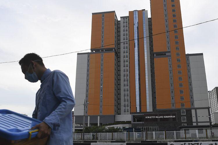 Seorang warga beraktivitas dengan latar belakang Wisma Atlet di Kemayoran, Jakarta, Rabu (18/3/2020). Pemerintah akan menyiapkan Wisma Atlet Kemayoran menjadi tempat isolasi masyarakat yang terjangkit COVID-19 guna menekan penyebaran virus tersebut lebih luas.
