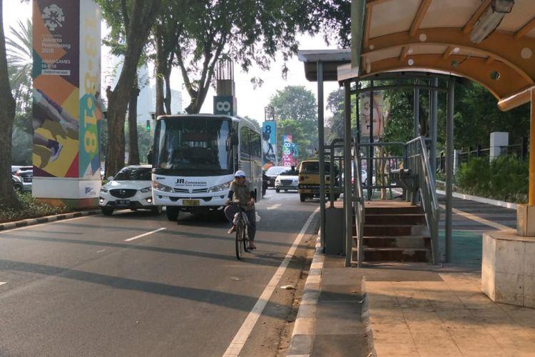 Seorang pesepeda bersepeda di ruas Jalan Asia Afrika, Senayan, Jakarta, Selasa (31/7/2018). Dia tidak menggunakan jalur sepeda di trotoar. Di sisi lain, jalur sepeda di trotoar itu juga terhalang tiang.