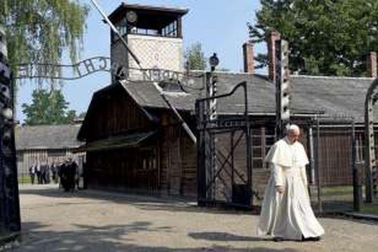 Paus Fransiskus berjalan sendiri melintasi gerbang kamp konsentrasi Auschwitz, Polandia dalam kunjungan bersejarah pada Jumat (29/7/2016).