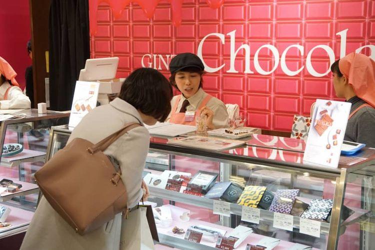 Seorang pengunjung perempuan tengah memperhatikan coklat yang ditawarkan di Ginza Mitsukoshi di Tokyo pada 7 Februari 2019.