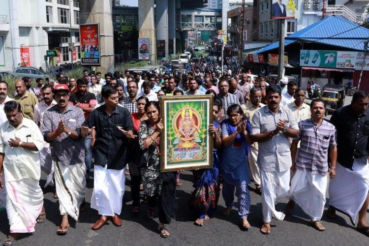Warga India membawa gambar Dewa Ayyappa saat demonstrasi menyusul masuknya dua wanita di kuil Sabarimala, di Kochi, Kerala, India, Rabu (2/1/2019). (AFP)