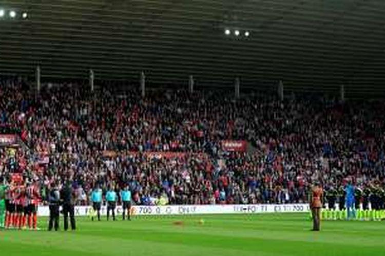 Pemain membentuk lingkaran dalam peringatan Remembrance Day dengan bunga poppy diletakan di tengah lapangan dalam pertandingan Premier League antara Sunderland dan Arsenal di Stadium of Light, Sabtu (29/10/2016).