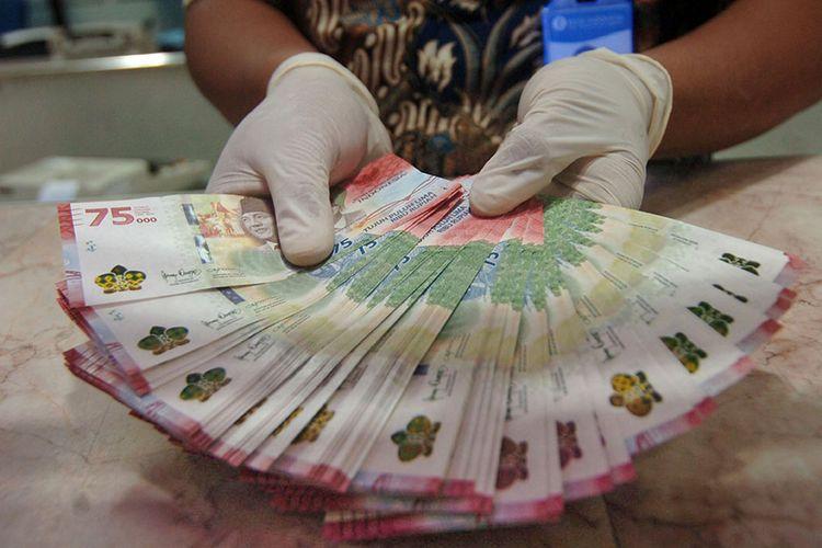 Petugas menunjukkan uang baru pecahan Rp 75.000 saat penukaran Uang Peringatan Kemerdekaan 75 Tahun Republik Indonesia di Kantor Perwakilan (Kpw) Bank Indonesia (BI), Tegal, Jawa Tengah, Selasa (18/8/2020). Kpw BI Kota Tegal menyediakan sebanyak 1,3 juta lembar uang baru pecahan Rp 75.000 untuk ditukarkan warga dengan syarat daftar online dan menunjukkan KTP elektronik.