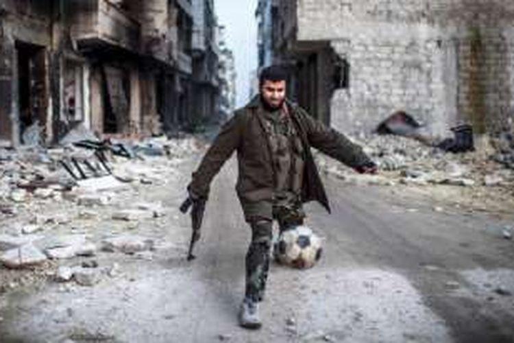 Seorang anggota pemberontak Suriah sedang bermain sepak bola di salah satu sudut Aleppo timur yang hancur lebur.