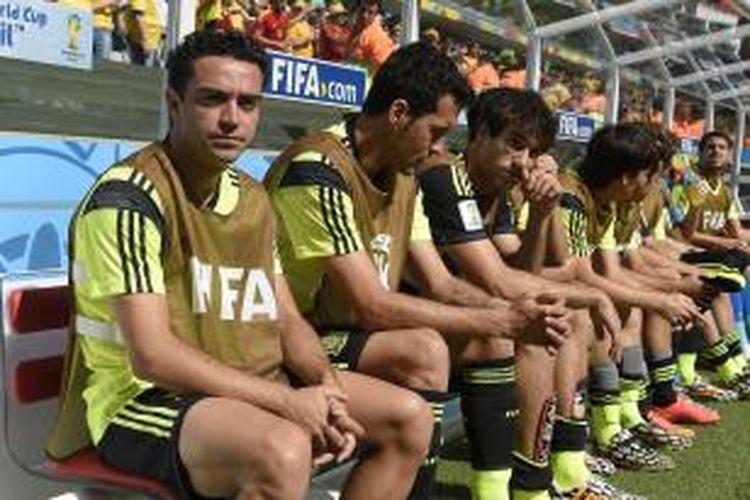 Gelandang tim nasional Spanyol, Xavi Hernandez (kiri), duduk di kursi cadangan pada pertandingan Grup B Piala Dunia melawan Australia, di Arena de Baixada, Curitiba, 23 Juni 2014.