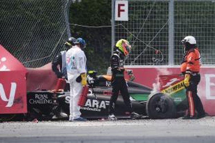 Pebalap Force India asal Meksiko, Sergio Perez (tengah), berjalan setelah keluar dari mobilnya yang mengalami kerusakan akibat kecelakaan pada GP Kanada di Sirkuit Gilles Villeneuve, Montreal, Minggu (8/6/2014).