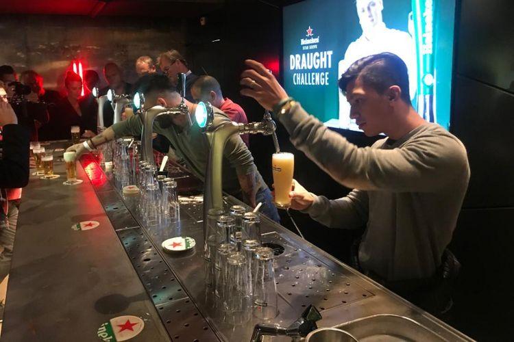 Bartender sedang menuang bir dari mesin draught.