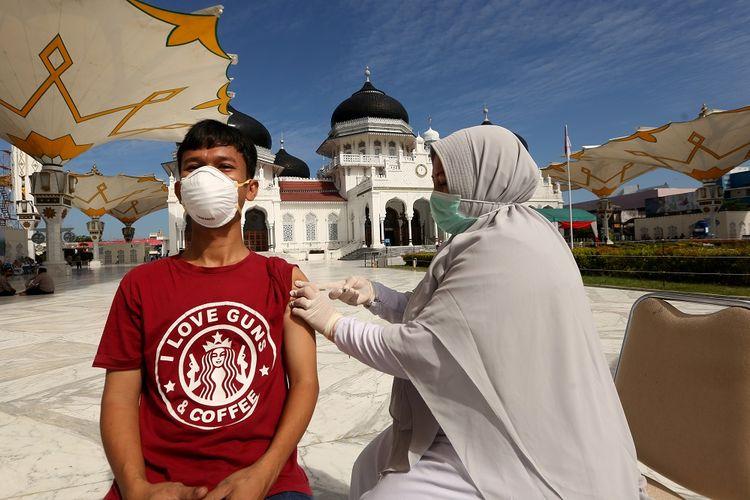 Warga mendapatkan suntikan vaksin COVID-19 oleh petugas kesehatan (kanan) pada vaksinasi merdeka di halaman masjid raya Baiturrahman, Banda Aceh, Aceh, Senin (6/9/2021). Vaksinasi merdeka yang digelar secara serentak pada 6-7 September 2021 di seluruh Indonesia merupakan program sinergi staf khusus Presiden bersama Kapolri dan  Panglima TNI untuk membantu pemerintah memutuskan mata rantai penyebaran serta penularan COVID-19. ANTARA FOTO / Irwansyah Putra/hp.