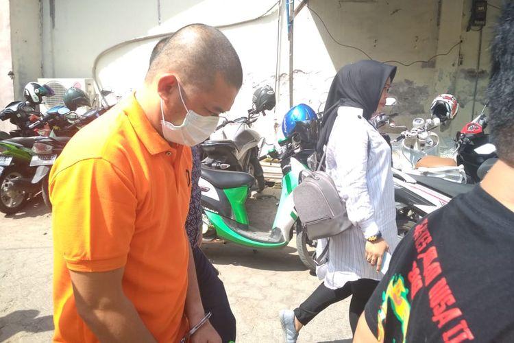 WJ (pakai masker) tertunduk saat dibawa ke klinik kejiwaan Rumah Sakit Bhayangkara Makassar oleh penyidik Polres Gowa, Selasa (26/3/2019).
