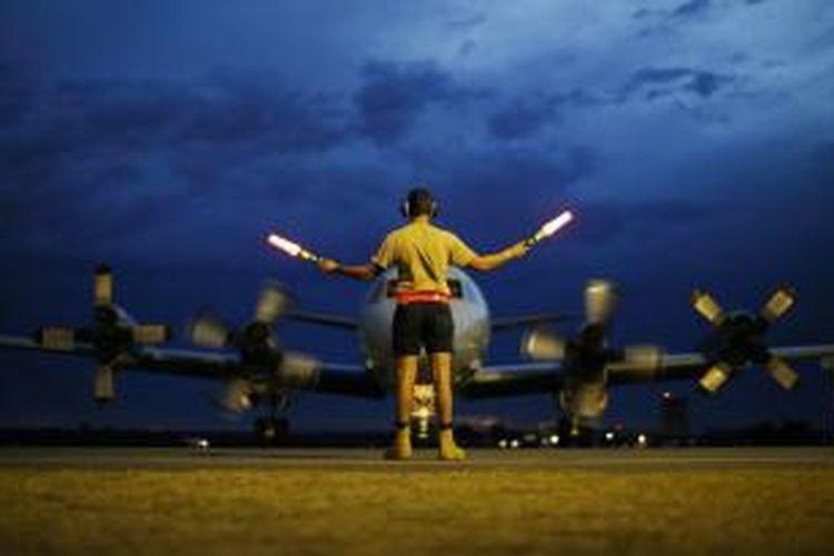 Seorang kru darat AU Australia sedang membimbing sebuah pesawat P-3C Orion yang baru kembali dari operasi pencarian Malaysia Airlines MH370 yang hilang di Samudra Hindia di pangkalan angkatan uadara Pearce di Bullsbrook, 35 kilometer sebelah utara kota Perth.