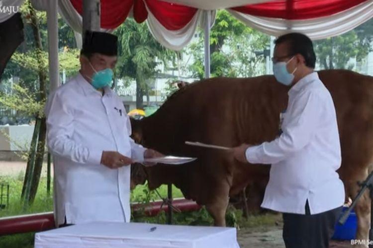 Kepala Biro Administrasi Sekretariat Presiden, Sony Kartiko menyerahkan sapi kurban Presiden Jokowi kepada Ketua Harian Badan Pengelola Masjid Istiqlal, K.H. Asep Syaifuddin, Senin (19/7/2021).