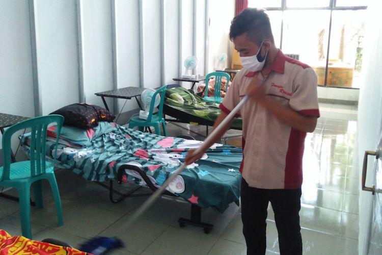 Petugas kebersihan saat membersihkan ruangan yang sudah disekat di gedung Korpri Lamongan.