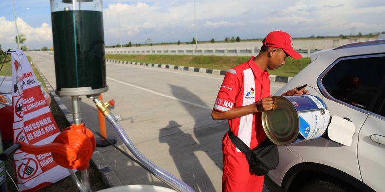 Petugas Mengisi bahan bakar di kios Pertamina di Jalan Tol Cikopo-Palimanan (Cipali), Jawa Barat, Kamis (15/6/2017). Kios Pertamina ini menyediakan BBM kaleng Pertamax, Pertamina Dex, dan Dexlite.
