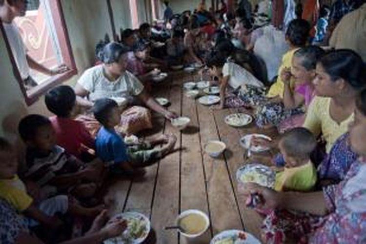 Keluarga muslim makan bersama di penampungan sementara di sebuah biara di Lashio di negara bagian Shan, Myanmar, 30 Mei 2013. Pasukan keamanan berpatroli setelah kerusuhan agama meletus yang menewaskan satu orang dan beberapa terluka.