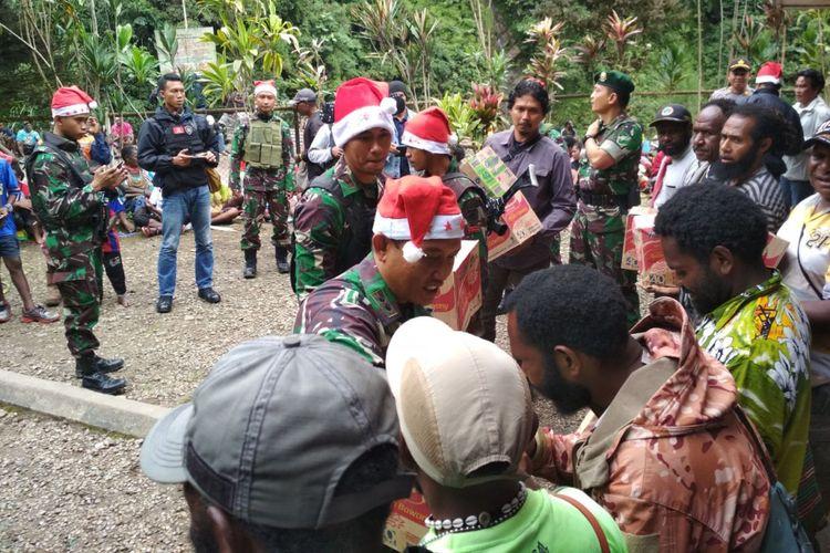 Dandim 1710/Mimika Letkol Inf. Pio Nainggolan bersama prajurit TNI membagikan bingkisan Natal kepada masyakat di Desa Banti, Sabtu (22/12/2018)