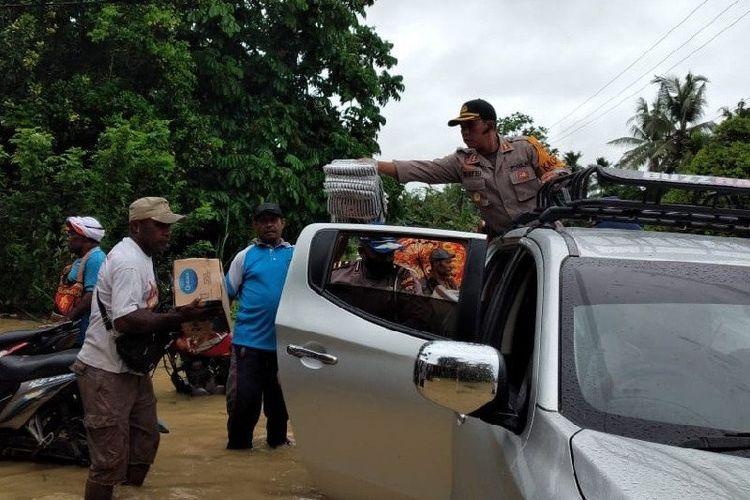Anggota Polres Keerom turut membagikan bantuan ke warga yang terdampak banjir.