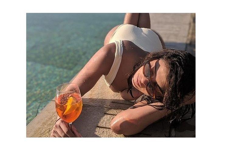 Priyanka Chopra berpose seksi dalam balutan one piece swimsuit dengan v-neck rendah.