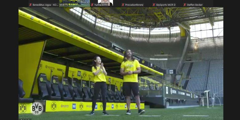 Legenda Borussia Dortmund, Patrick Owomoyela, menunjukkan sisi lapangan dan bench pemain di Stadion Signal Iduna Park.