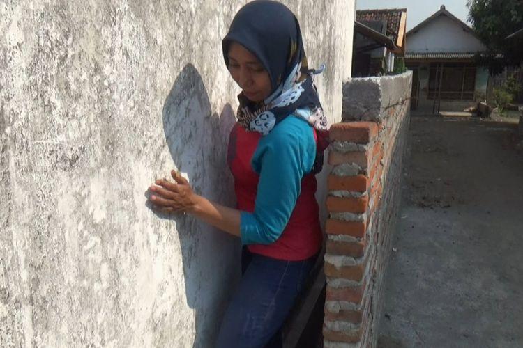 Siti Khotijah, warga Desa Sudimoro, Megaluh, Jombang, Jawa Timur, saat keluar dari rumah melalui celah antara rumah kerabatnya dengan tembok yang dibangun tetangganya.
