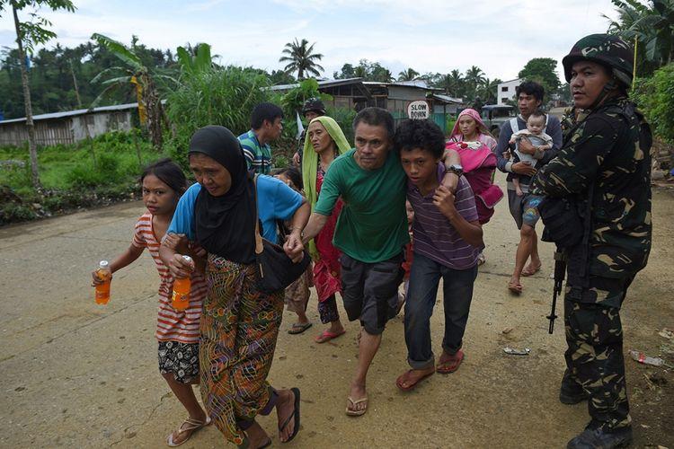 Seorang tentara berjaga saat warga berjalan menuju sebuah truk setelah diselamatkan dari rumah mereka di sebuah desa di pinggiran Marawi, Filipina, Rabu (31/5/2017). Pertempuran berdarah terjadi antara militer Filipina dengan pasukan Maute di Marawi dalam upaya menangkap pemimpin kelompok Abu Sayyaf, Isnilon Hapilon.