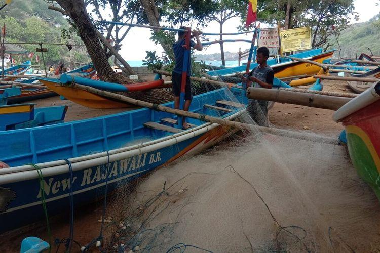Nelayan memperbaiki Jaring di Pantai Baron, Gunungkidul Kamis (29/7/2021)